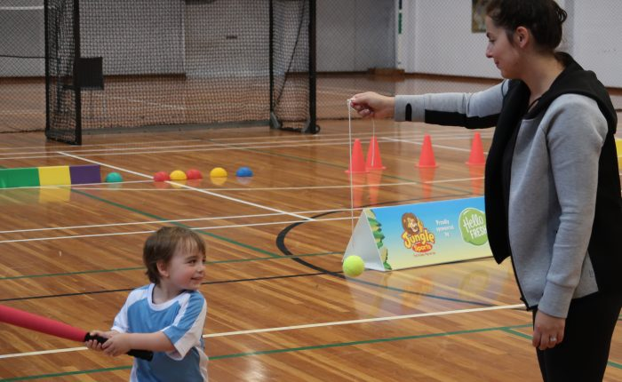 child playing t-ball with mum
